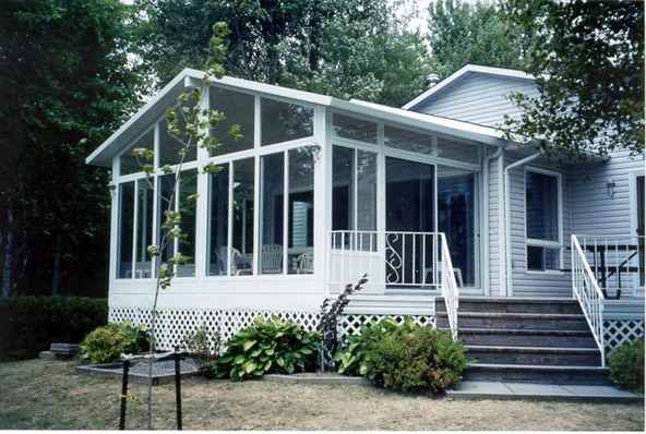 3 season glass sunroom with gable roof line, glass side slider windows and glass transoms.